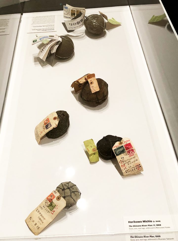 """Michio Horikawa, works from various iterations of """"The Shinano River Plan,"""" a mail-art project that began in 1969; stones, wire, and paper tags; objects sent by postal mail and addressed to artists and other recipients (various collections, photo by the author for Hyperallergic)"""