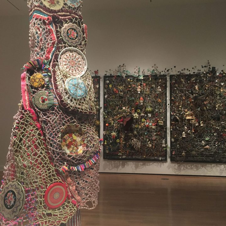 "Nick Cave, detail of ""Soundsuit"" (2015), mixed media, including enameled can lids, macramé, shoelaces, plastic beads, metal, and mannequin in front of ""Wall Relief"" (2013), mixed media, including ceramic birds, metal flowers, afghans, strung crystals, and gramophone"