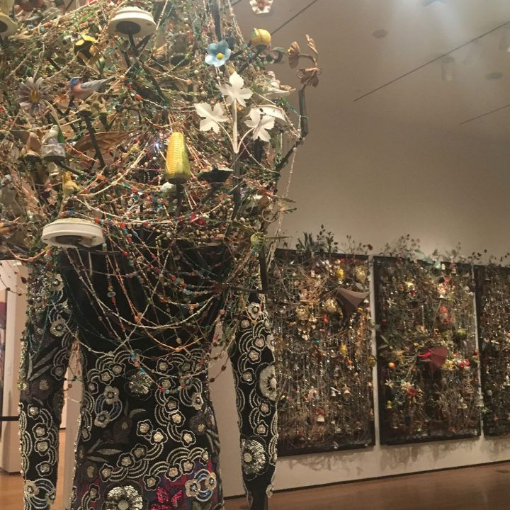 "Nick Cave, detail of ""Soundsuit"" (2013) across from ""Wall Relief"" (2013), mixed media, including ceramic birds, metal flowers, afghans, strung crystals, and gramophone"