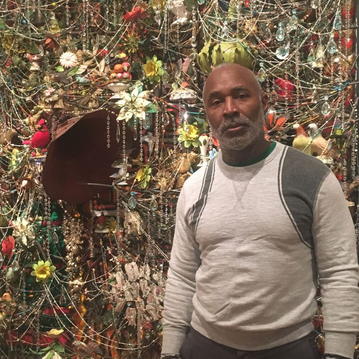 "Nick Cave and ""Wall Relief"" (2013), mixed media, including ceramic birds, metal flowers, afghans, strung crystals, and gramophone (photo by the author for Hyperallergic)"