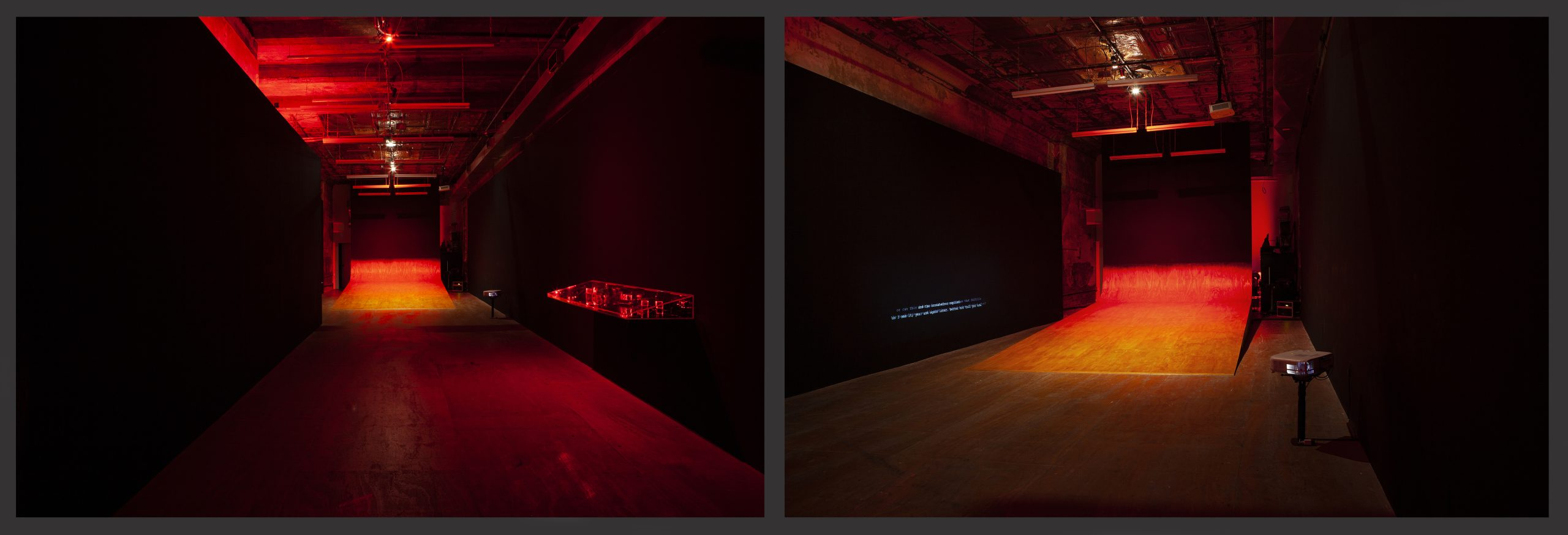 Views of a dark gallery space, filled with red light, host a large wooden ramp curling up the back wall. On the right is a mounted clear case glowing with red lasers; overlapping white and grey text is projected on the left wall.