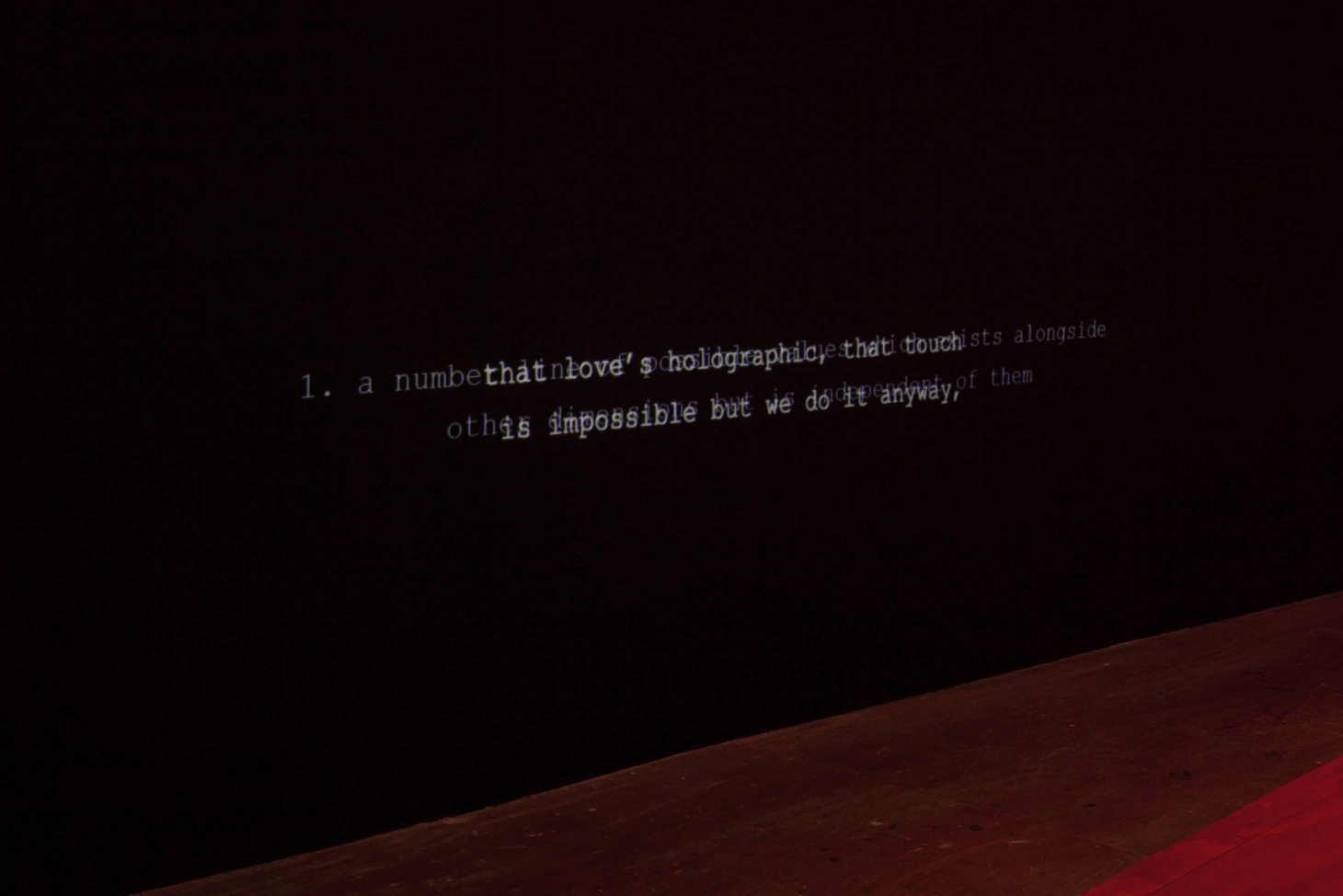"""A black wall softly lit with red light shows two lines of white captions, reading: """"that love's holographic, that touch is impossible but we do it anyway"""" which overlap a second projection of illegible text."""