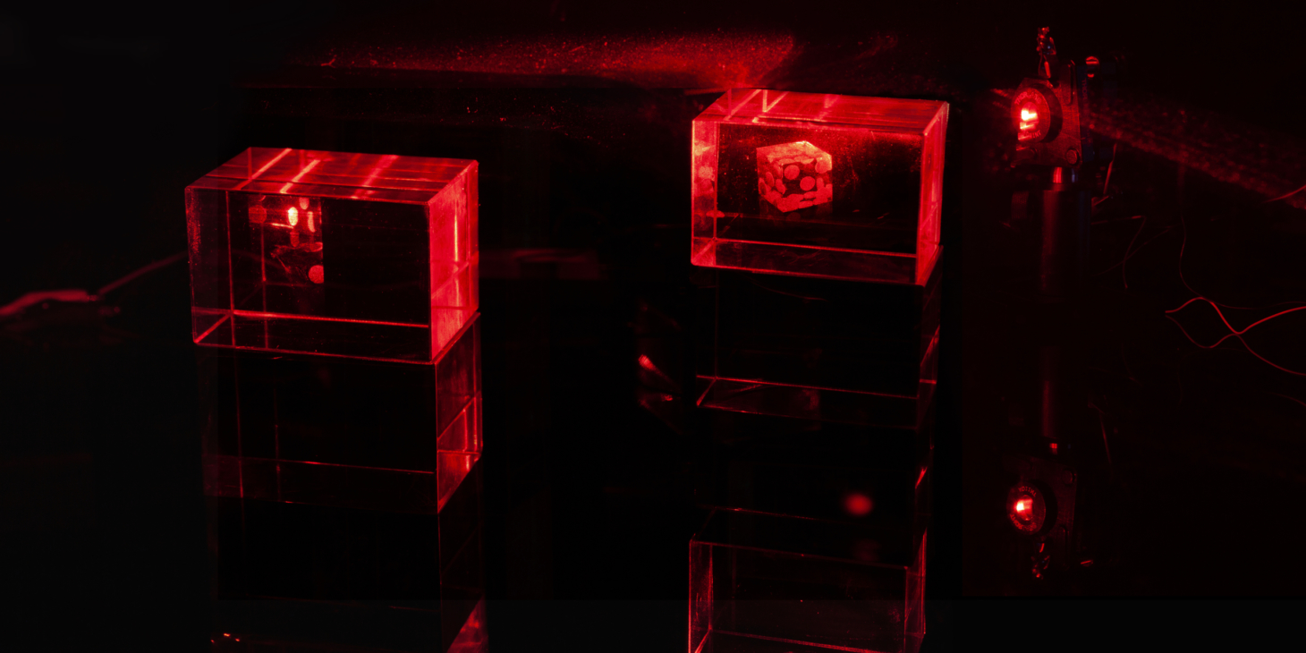 Two glowing holograms are lit by red lasers. One image of a single die is rendered in full while the second image of several dice is displayed in the same light path and partially occluded by the shadow of the first mount.