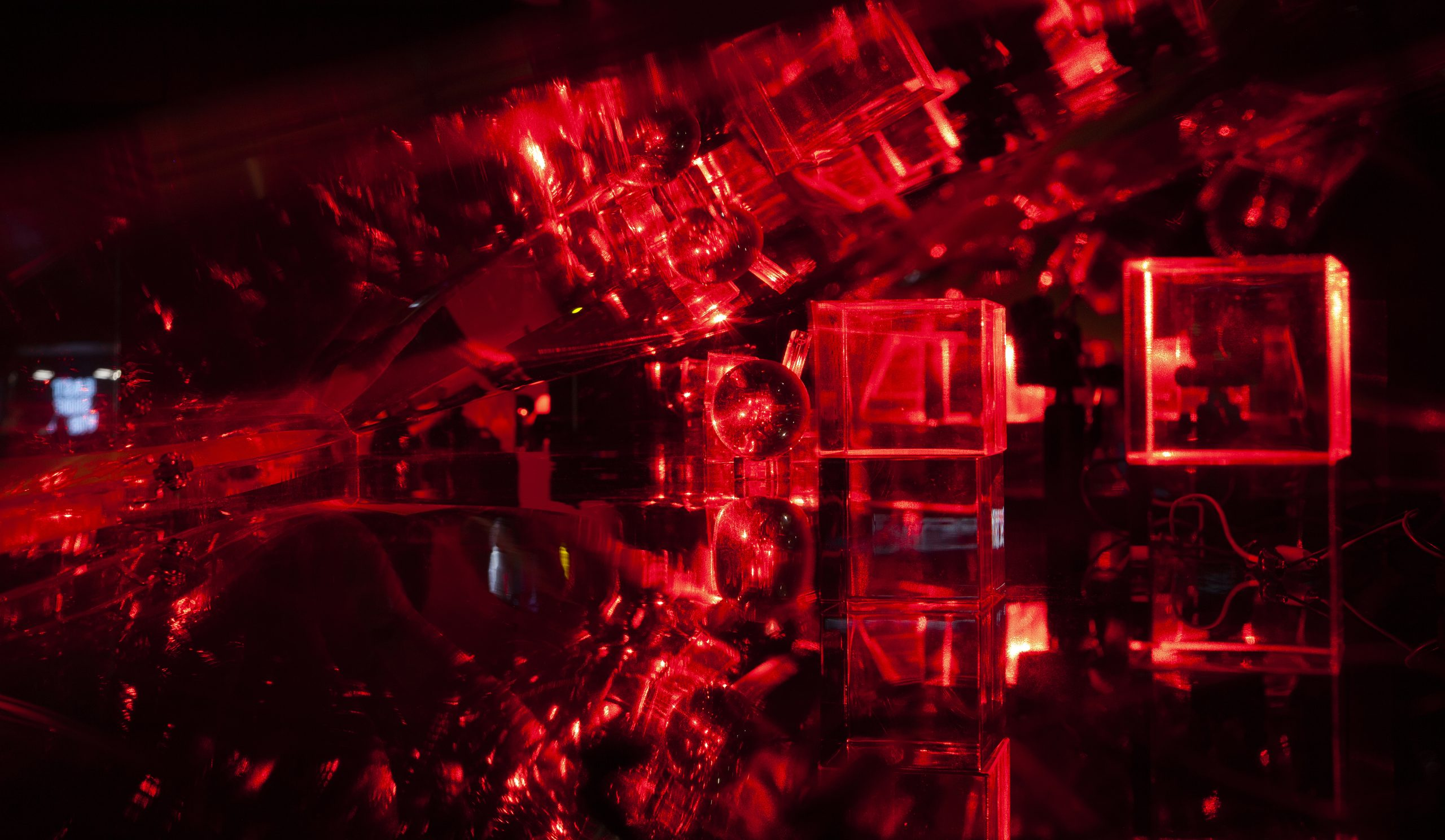Clear cubes and a crystal ball lit by red lasers on black ground reflect into an endless circular pattern in a long clear sloped case that recedes into space.