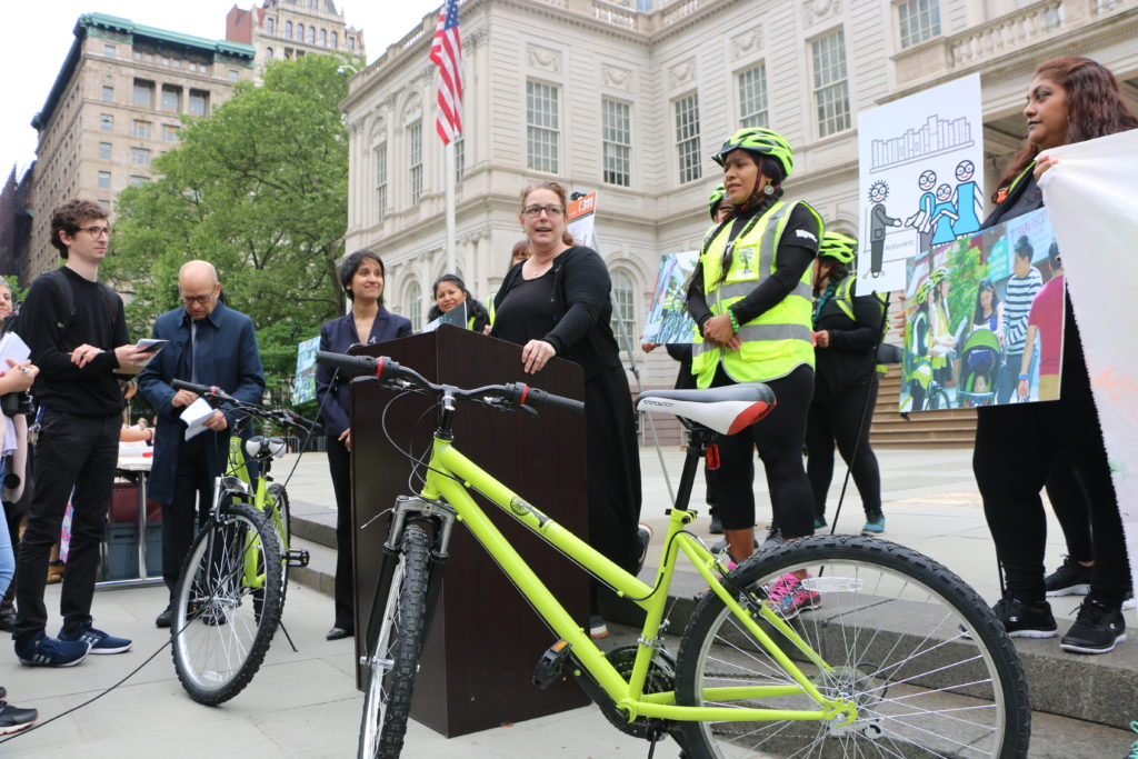 Tania Bruguera stands at a podium with administrators and cyclists. a lime green bicycle sits, riderless, in the foreground.