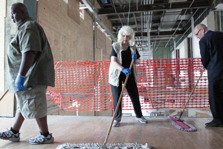 An older white woman sweeps the floor in front of a red plastic barrier.